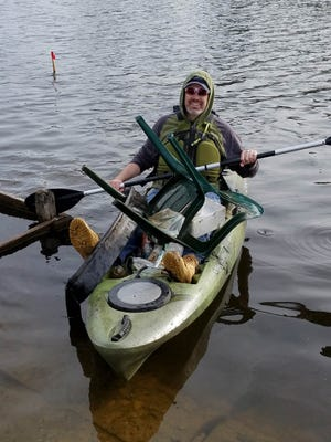 Brighton City Manager Nate Geinzer paddles back to shore after fishing a load of garbage out of the Mill Pond Saturday, April 22, 2017. The city is embarking on a project to clean up and restore the  pond and surrounding area.