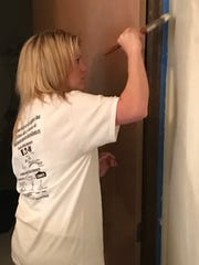 Shayna McArthur, LOC Federal Credit Union business development manager, takes care of a bedroom wall.