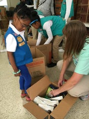 Girl Scout troop 4612 member Jada Hill, 6, left, receives help while packing Girl Scout cookies to send to troops serving overseas on Sunday.