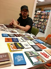 Jason Tagmire, owner of card game company Button Shy, sits among his company's wallet games in a small office in Tiki Tiki Board Games in Woodbury.