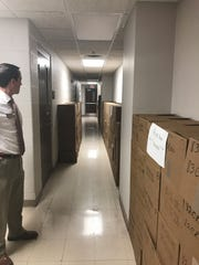 Henderson Circuit Clerk Herb McKee Jr. looks at boxes filled with old cases marked for storage in Frankfort