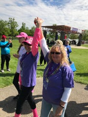 Lisa Cummins (right) and Diane Ordiway triumphantly make their way through the Survivor's Lap.
