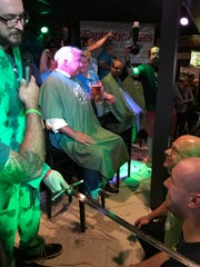 St. Baldrick organizer Robb Drzewicki dubs Vince and Shaun Austin as Knights of the Bald Table for their seven years of participation in the event.