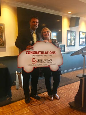 Adamm Davis, general service manager of Suburban Imports of Troy gifting Nancy Kocsis, ASD advisor of Birmingham School District, a no-cost vehicle lease of her choice, compliments of The Suburban Collection for being honored as Teacher of the Year.