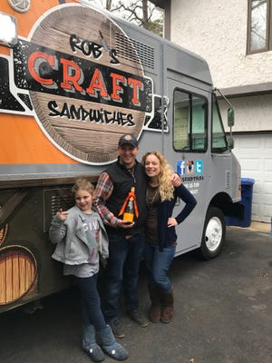 Rob, Kim and Giana, 7, show off their new food truck, Rob's Craft Sandwiches, in their Medford driveway. The truck has attracted a lot of interest in the neighborhood.