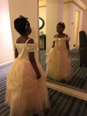 "In a hotel room in New York City in February 2016, Chika, 6, tries on her fancy, frilly dress that is a replica of Belle's dress from ""Beauty and the Beast."" She stares at herself for a long time in the mirror. It was her favorite dress. ""You're a princess, Chika,"" Janine Albom tells her. And Chika beams at the compliment."