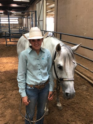 Novice's Hadley Clearman stands with Lexus at the Taylor County Expo Center's Horse Barn. Clearman rides Lexus for the break-away roping competition. She is also competing in the reined cow horse and girls cutting at the Texas High School Rodeo Association Finals this week.