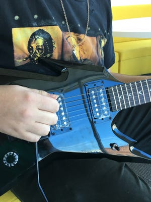 Johnny Crow holds the guitar his late father bought him for his birthday. A video of Johnny receiving it has gone viral.