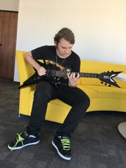 Johnny Crow, 16, strums his guitar inside the Times Herald June 8. A video of the teen receiving the guitar as a birthday gift from his late father has gone viral.