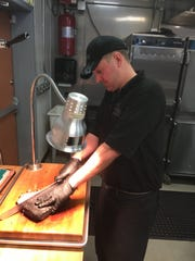 "In this file photo, Kyle ""Tex"" Mayo, co-owner of CJ's BBQ Smokehouse, slices into a brisket."