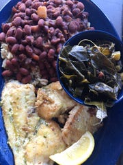 """The Dixie Fish Co.'s signature specialty is hogfish, prepared here """"The Dixie Way"""" in garlic butter and served with collard greens and a spicy red beans and rice."""
