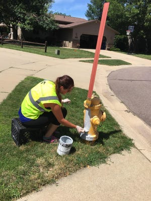 Riley Carr with the city of Sioux Falls repaints a fire hydrant on June 20, 2017.