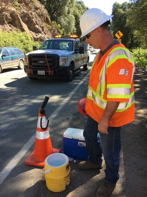 California Department of Transportation employee Brett Smith of Cottonwood takes a break from his flagging duties on Highway 299 to check his 2-gallon water container on a warm Thursday morning.