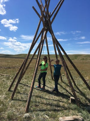 Jillian Cockman and Abby Hutton celebrate under the tepee poles at the Graham Ranch. The canvas fit perfectly around these poles and the campout was a success. Abby said even s'mores taste better in a tepee.