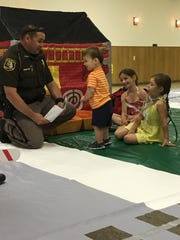 Will Dimick, 1 (center), and his sisters, Josephine, 6 (center), and Genevieve, 4 (right), learn about law enforcement, strangers and gun safety from police officers in Safety Town.