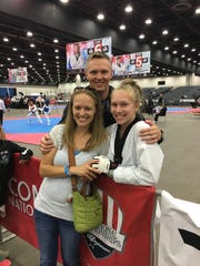 Natalie Hershberger celebrates her USAT national championship in Detroit this month with her mother, Nicole, and father/coach Chris.