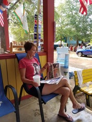 Melissa Williams, wife of columnist Ben Williams, reads the daily Fair Times, published only during the Neshoba County Fair.