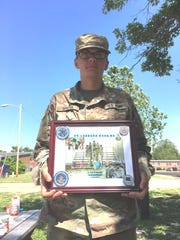 Private Brian William Sproul, a 2015 Washington High School graduate, holds a plaque recognizing Greenwood Elementary School in Princess Anne, after its students sent more than 200 encouraging letters to service members at his basic training location.