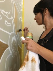 Amanda Giacomini, an artist and yoga celebrity known for her 10,000 Buddhas mural project, paints a wall at La Quinta  Resort. (June 2017)