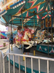Milly Kincaid, 3, rides the merry-go-round with her grandmother, Nancy Green. The family stays in the area each summer, coming up from Fort Lauderdale, Florida.