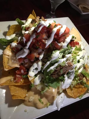 """It's Mine, Nachos at Ole Fire Grill in Melbourne was a substantial plate of pork, corn tortillas, cheese sauce (""""queso""""), shredded lettuce, jalapeños, pico and sour cream."""