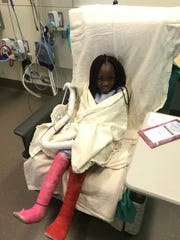 Seven-year-old Ainata smiles as she prepares for surgery