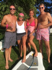 Fuzzy Marek, Anne Pierson, Gretchen Marek and Warren Pierson pose for a photo after racing on a stand-up paddleboard.