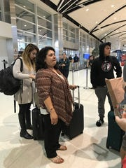 Lourdes Salazar Bautista, 49, at Detroit Metro Airport on Aug. 1, waiting to take flight to Mexico. On left is her oldest daughter, Pamela, 19, and on right is her son, Bryan, 13.