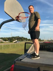 Wes Davidson attaches a new net to a basketball hoop