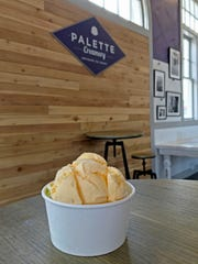 A scoop of Orange Blossom Mango sits atop a scoop of