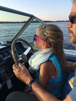 Maya Wood helps Douglas Wood pilot the boat on Rainy Lake.