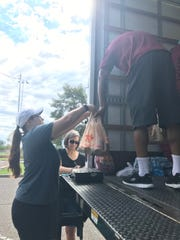 Volunteers help weigh and load food into a truck Aug.