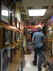 Henry Mullenax walks through his basement hallway on Sunday, Aug. 13, 2017. A car enthusiast and collector and former driver for Conway Twitty, Mullenax has been collecting country music star memorabilia for more than 25 years.