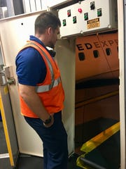 Thomas Stearly, a United Ground Express employee, waits for gate-checked carry-on bags to arrive at the jet bridge at Willard Airport on Saturday, Aug. 12, 2017. The flight arrived from O'Hare International Airport in Chicago.