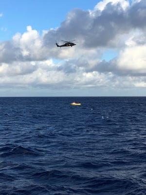 In this photo released by the U.S. Coast Guard, a UH-60 Black Hawk helicopter aircrew from Wheeler Army Airfield and a fireboat crew from the Honolulu Fire Department conduct a search for five crew members aboard a downed Army UH-60 Black Hawk helicopter approximately two miles west of Kaena Point, Oahu, Hawaii, Wednesday, Aug. 16, 2017. A multi-agency team scoured the ocean off Hawaii on Wednesday for the soldiers aboard the Army helicopter that went down during a nighttime training exercise.