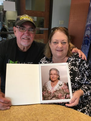 Dan and Sandra Gaspard hold a photo of Ednes Gaspard, who was a traiteur or faith healer in the Maurice community.