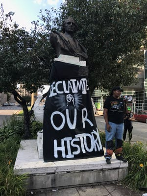 Lynx McChea speaks before a crowd of several dozen demonstrators on Saturday Aug. 19, 2017, who favor the removal of this Christopher Columbus monument