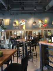The majority of the seating at The Hop Grenade Taproom consists of high top tables and fun hop-themed art throughout.