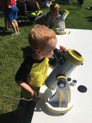 Evan Blumberg, four, of Greencastle talks a look at the moon passing in front of the sun through a telescope at Renfrew Institute, Waynesboro, on Aug. 21, 2017.