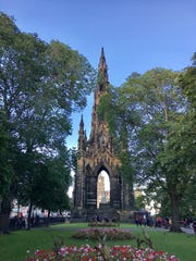 Tourists gather around the Sir Walter Scott Monument
