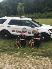 Officers Cara Butts and Jon Dailey are seen with their prospective K-9 partners, both of the Belgian Malinois breed, somewhat smaller than a typical German Shephard.