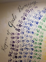 """Inside First Congregational Church of Wauwatosa, a mural of colorful handprints bears the title """"Keepers of God's Promises."""""""