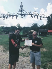 "Elijah Daniel, left, shakes hands with local business owner John Colone in 2017 when Daniel was declared temporary ""mayor"" of Hell, Mich."