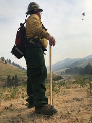 Firefighter Tyler Anderson watches as a helicopter