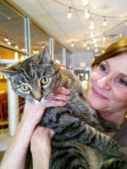 Annette Gries with adoptable River Kitty cat, Thomas. It's all about the cats at the Kitty Cafe.