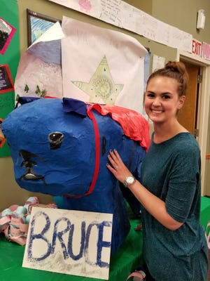 Social worker Kelly Nilsen with Bruce, a blue paper mache bulldog created by members of her empowerment support group.