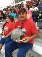 Tony Valenzuela holds his old football helmet from when he played in 1969.