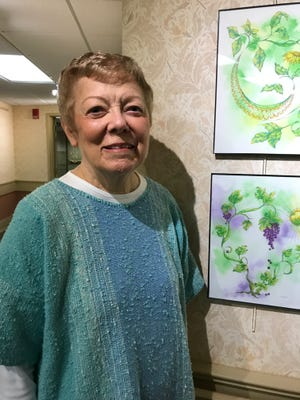 Givens Estates artist Elizabeth Rosson stands next to two of her works.