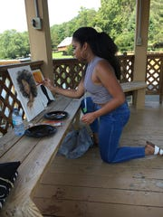 Proctor Institute Intern Krystal Jackson, 21, takes a break from her duties to paint a picture at the Haley Farm lake gazebo. Photo: Avis