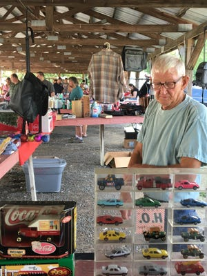 Joe Hensley mans his booth at the Greenbrier Flea Market as customers take in the sights on a recent Saturday.